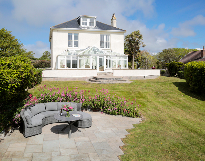 The large sunny garden with outdoor seating at The Haven self catering holiday home in Daymer Bay on the north Cornwall coast.