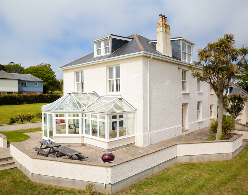 The external view of The Haven holiday home in Daymer Bay with outdoor seating area, BBQ and large garden.
