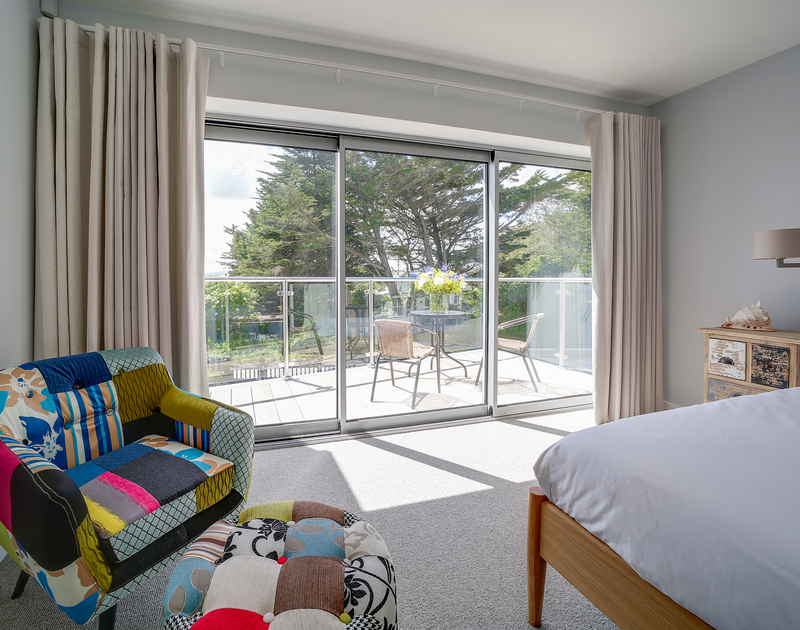 The master bedroom with superking size bed, terrace and ensuite shower at Morwenna holiday home in Daymer Bay.