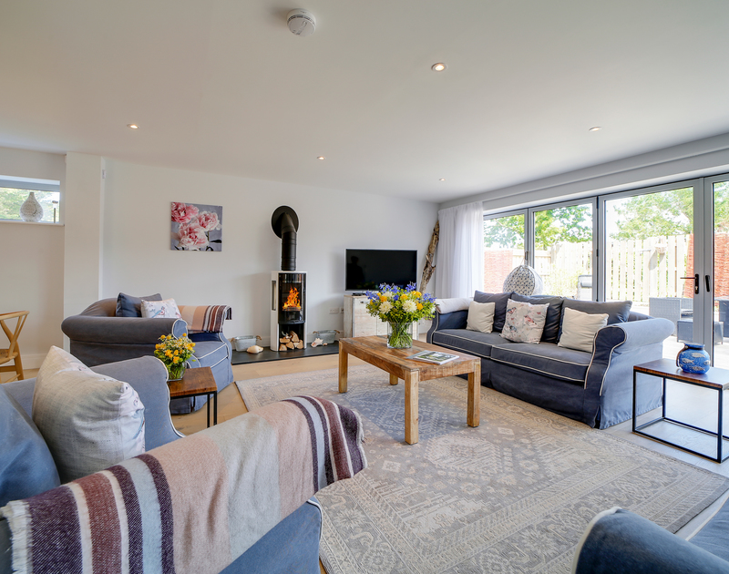 The cosy lounge with wood burner at Morwenna holiday home, Daymer Bay, North Cornwall.