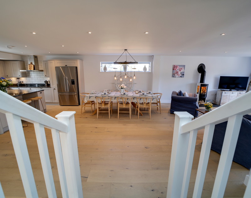 The stairs leading down to the light filled open plan living kitchen and dining room at Morwenna holiday home in Daymer Bay, Rock.