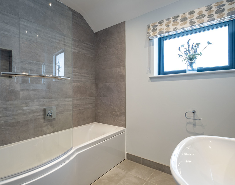The family bathroom with bath and overhead shower at Tor View holiday home in St Minver, Rock.