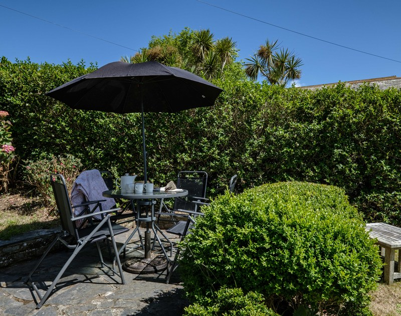 The sunny terrace with outdoor seating at Penventon holiday home in Port Isaac.
