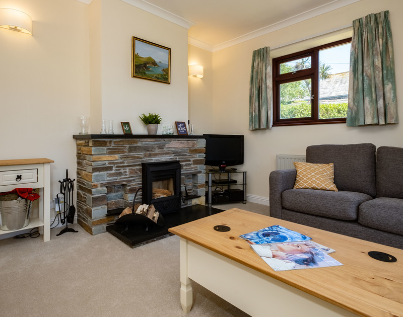 The comfortable living room with a cosy log burner at Penventon holiday home in Port Isaac.