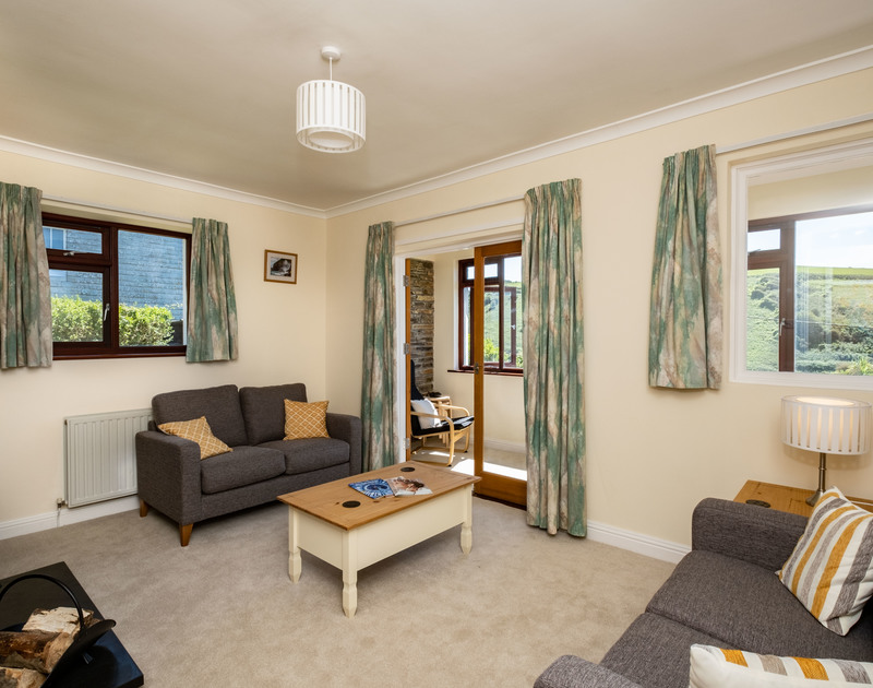 The lounge with doors leading to the sunroom at Penventon holiday home in Port Isaac, on the north Cornwall coast.