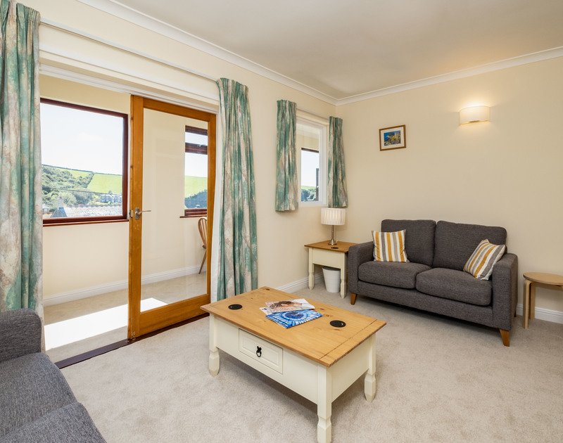 The lounge with doors leading to the light and airy sunroom at Penventon self catering holiday home in Port Isaac, Cornwall.