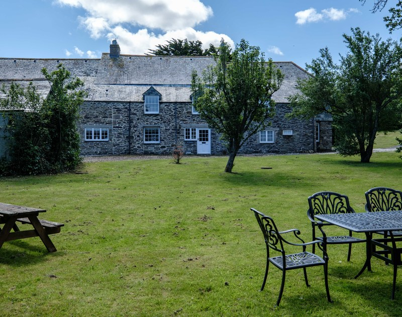 The large garden with outdoor seating areas at The Farmhouse holiday home in St Minver, Rock.