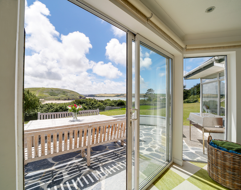The patio doors leading to the sunny terrace and outdoor seating area at Sandy Lodge self catering holiday home in Daymer Bay, Cornwall.