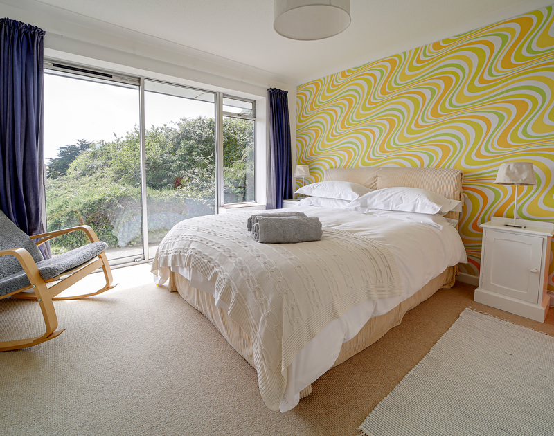 The bedroom with patio doors leading to the garden at Sandy Lodge self catering holiday home in Daymer Bay, North Cornwall.