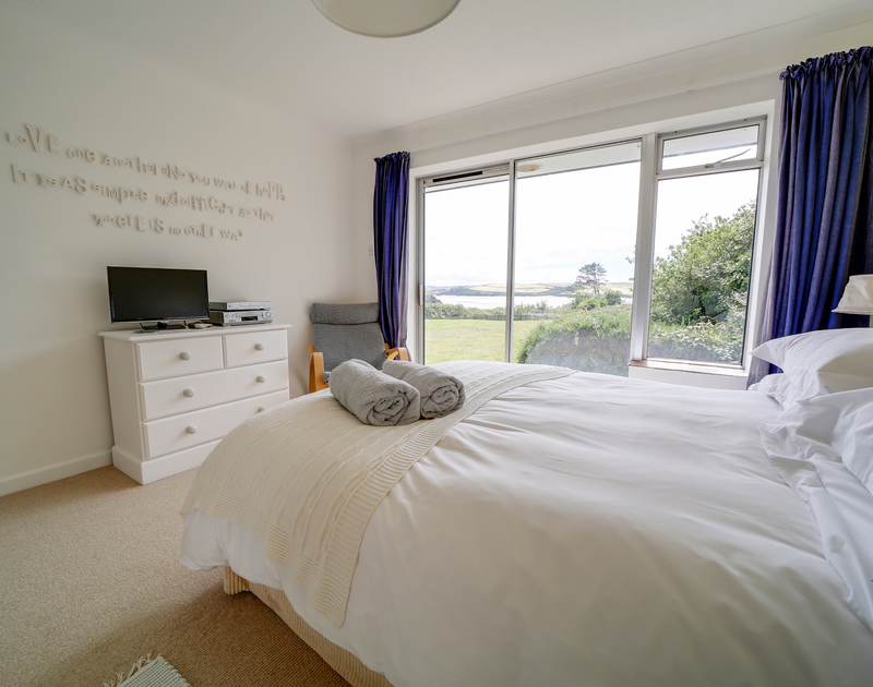 The king size bedroom with patio doors out to the garden at Sandy Lodge holiday home in Daymer Bay.