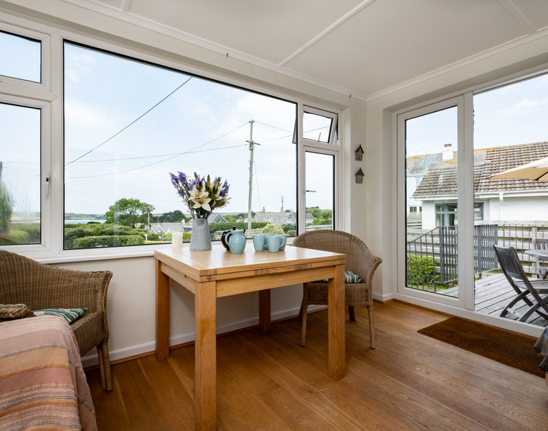 The light filled sunroom with doors to the patio at Croft Elms self catering holiday home in Daymer Bay.