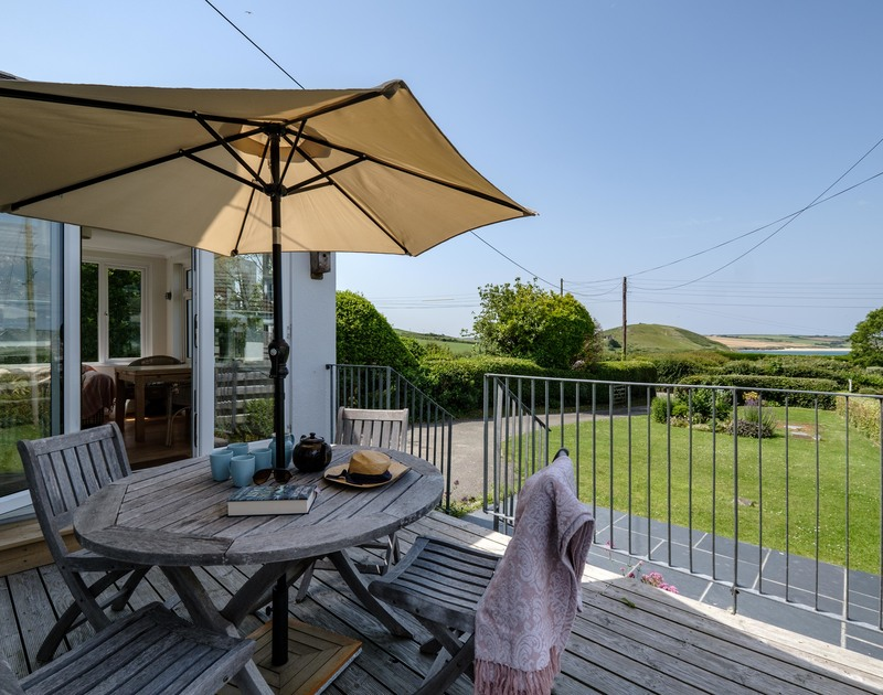 The patio doors leading to the outdoor seating area with views over Daymer Bay at Croft Elms self catering holiday home in North Cornwall.