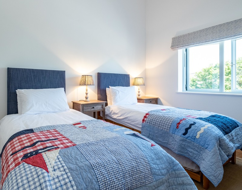 The twin bedroom with pullout beds and an ensuite bathroom at Artemis self catering holiday home in Rock, North Cornwall.
