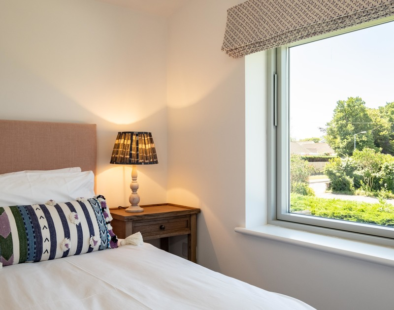 The twin bedroom with lovely large windows at Artemis self catering holiday home in Rock, North Cornwall.
