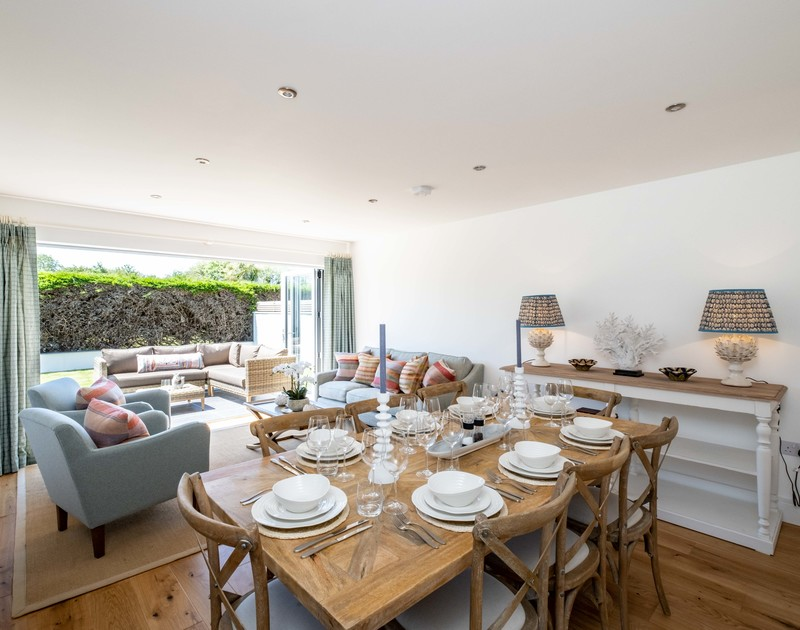 The spacious dining / lounge with large doors leading to the patio at Artemis self catering holiday home, North Cornwall.
