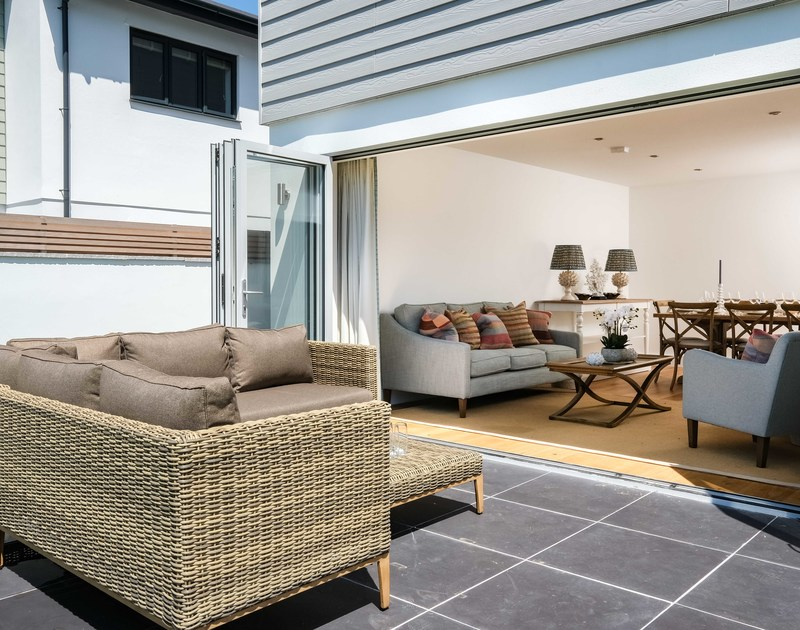 Patio doors leading to the outside seating area and garden at Artemis self catering holiday home in Rock.