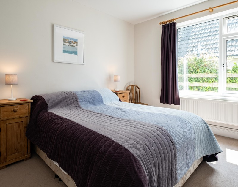 The king size bedroom with an en-suite bathroom at Lerryn, a self catering holiday property in Rock, North Cornwall.