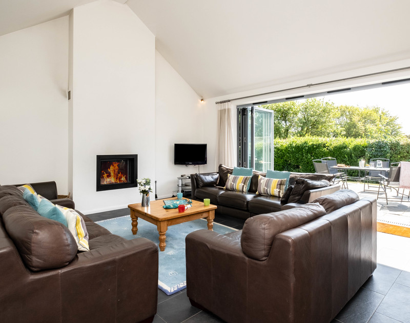The light filled lounge with bi-fold doors opening to the patio and garden at Lerryn self catering holiday home in Rock, North Cornwall.