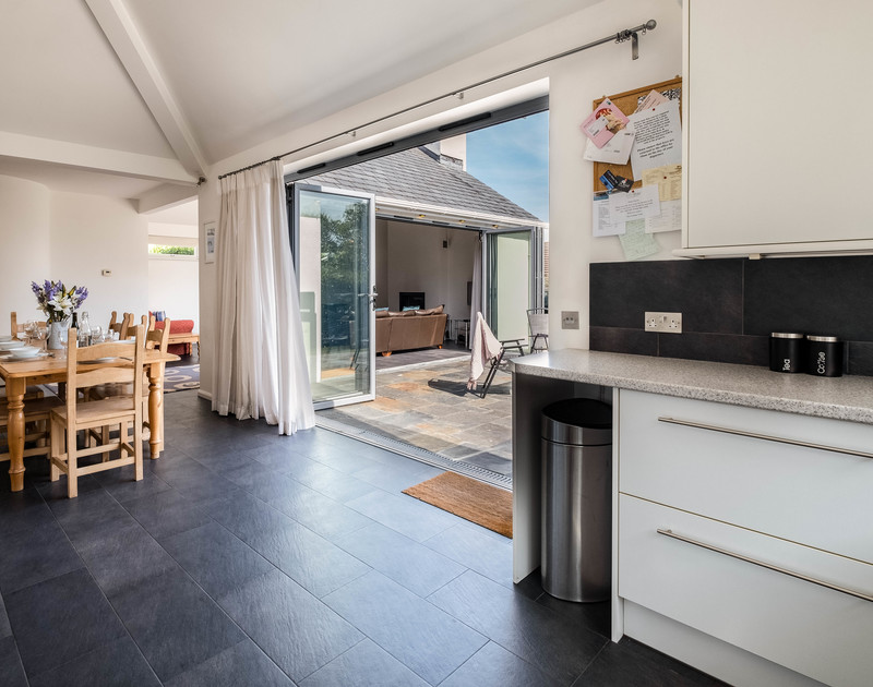 The open plan kitchen, dining and lounge area with large doors at Lerryn self catering holiday home in Rock, North Cornwall.