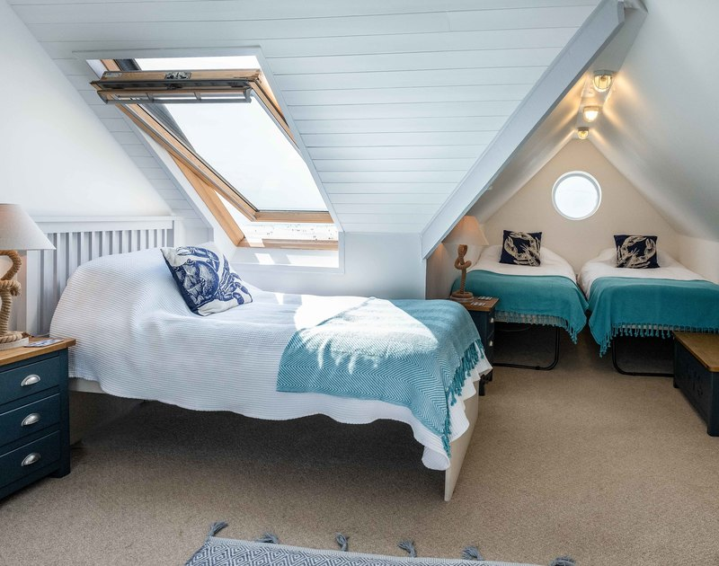 A light, fresh twin bedroom at Balderstone, a holiday house in Polzeath, Cornwall, with its velux window.