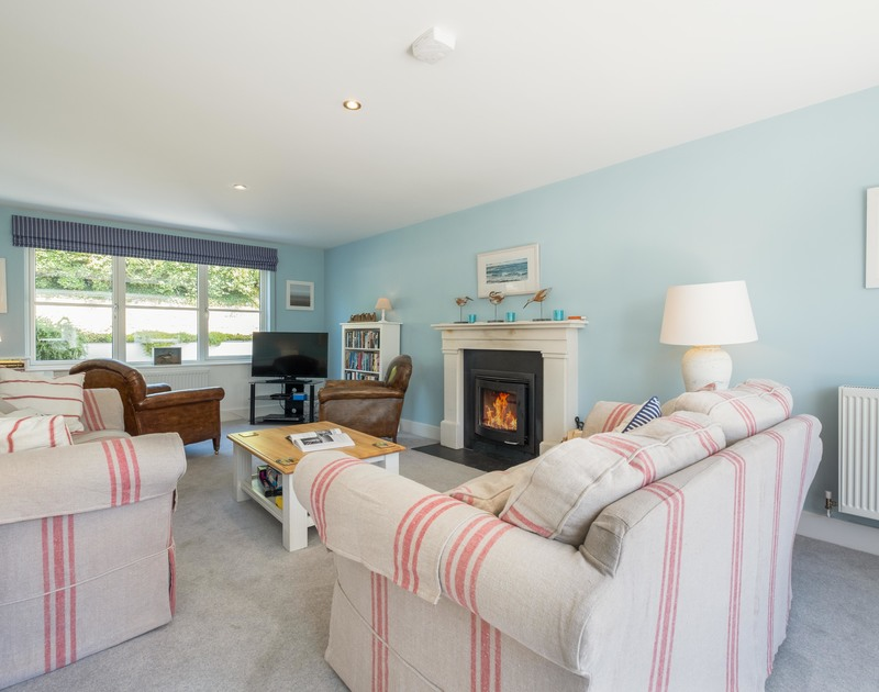 The living room with fire and patio doors at Cherrytrees self catering holiday home in North Cornwall.