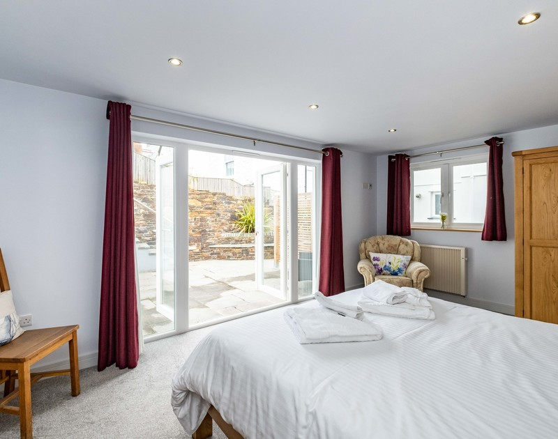 The master king bedroom with french doors opening on to the patio at The Hideaway self catering holiday cottage in Port Isaac, North Cornwall.