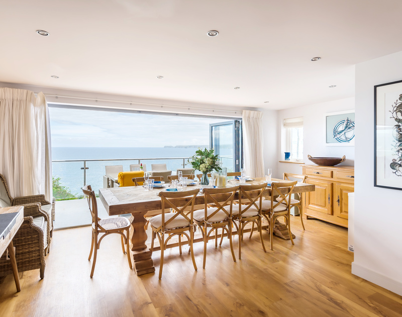 The dining room with sea views and bi-fold doors on to the patio at The Lawns self catering holiday home in Port Isaac in North Cornwall.