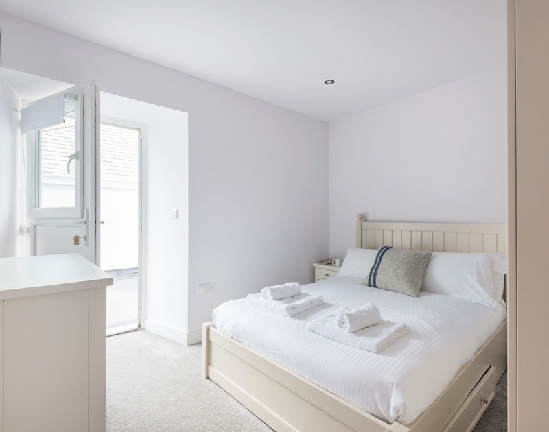 The second double bedroom with ensuite bathroom and doors on to the top patio at The Lawns self catering holiday home in Port Isaac in North Cornwall.