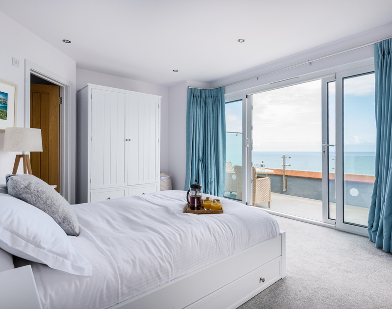 The master bedroom with ensuite bathroom and private balcony with sea views at The Lawns self catering holiday home in Port Isaac in North Cornwall.