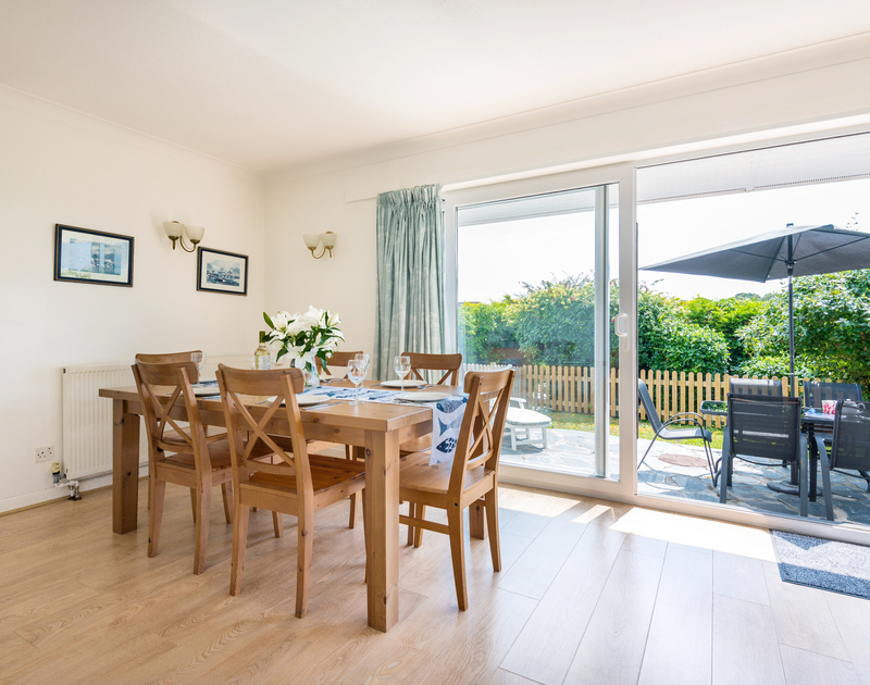 The light filled dining room with sliding doors leading to the garden at Tremay self catering holiday home in Rock, North Cornwall.