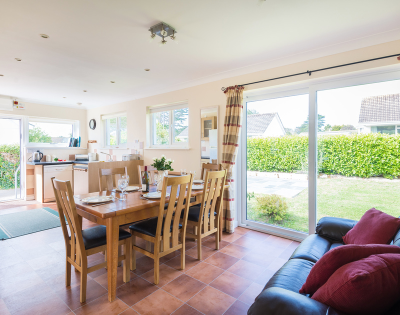 The open plan kitchen and dining room with patio doors to the front garden at Chimings self catering pet-friendly holiday home in Rock, North Cornwall.