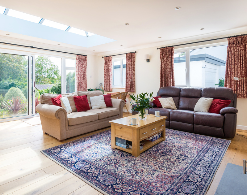 The living room with patio doors to the back garden at Chimings self catering pet-friendly holiday home in Rock, North Cornwall.