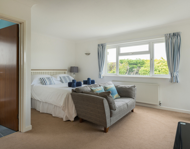 The king size bedroom with ensuite and doors to patio at Tremay self catering holiday home in Rock, North Cornwall.