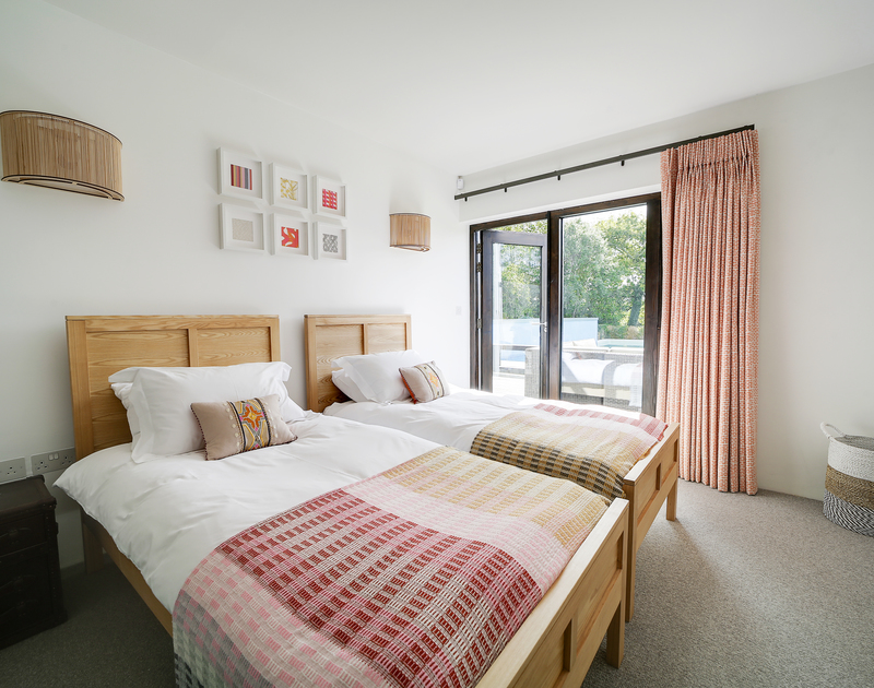 The twin bedroom with access to the garden and pool area at Tresithney self catering holiday home in Rock, North Cornwall.