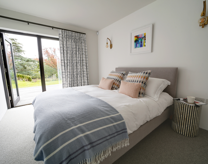 The king bedroom with a shower room ensuite and access into the garden and pool area at Tresithney self catering holiday home in Rock, North Cornwall.