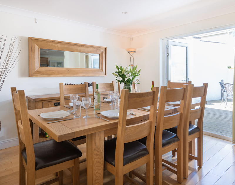 The dining area with outdoor access at The Chalet self catering holiday home in Polzeath, North Cornwall.