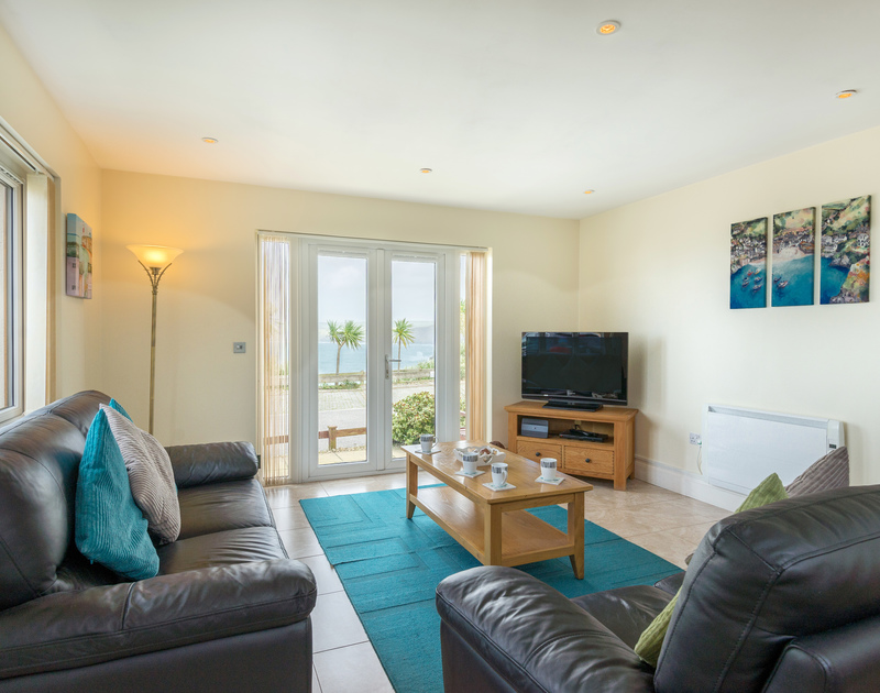 The open plan living room, kitchen and dining area with sea views at Sea Gem self catering holiday home in Port Isaac, North Cornwall.
