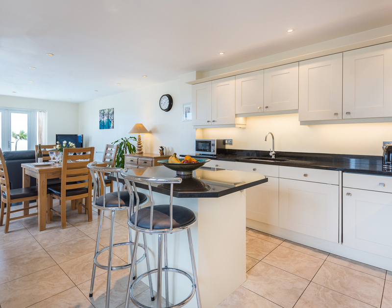 The open plan living room, kitchen and dining area at Sea Gem self catering holiday home in Port Isaac, North Cornwall.