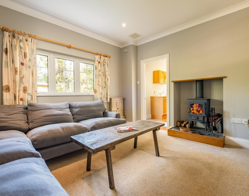 The lounge room with a cosy log burner at Carrek House self catering holiday home in Rock, North Cornwall.