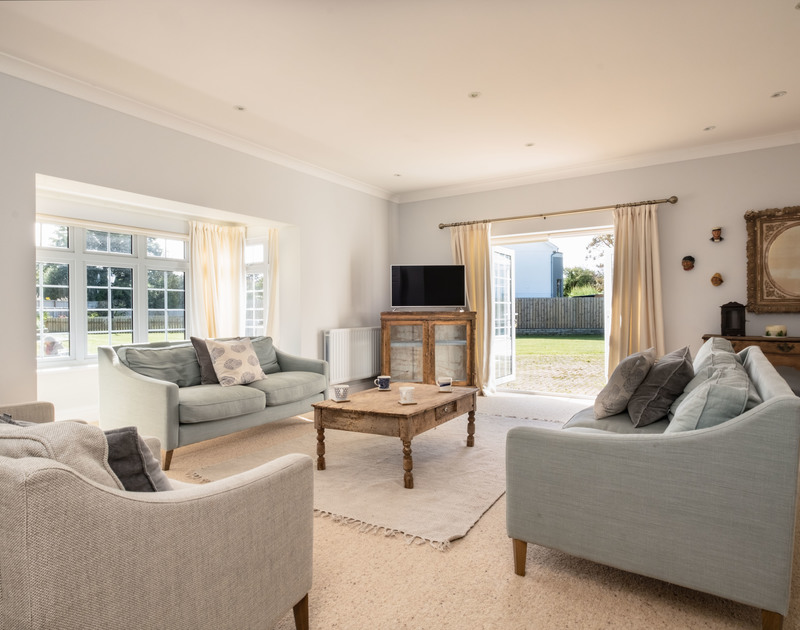 The beautiful living room with access to the garden at Carrek House self catering holiday home in Rock, North Cornwall.