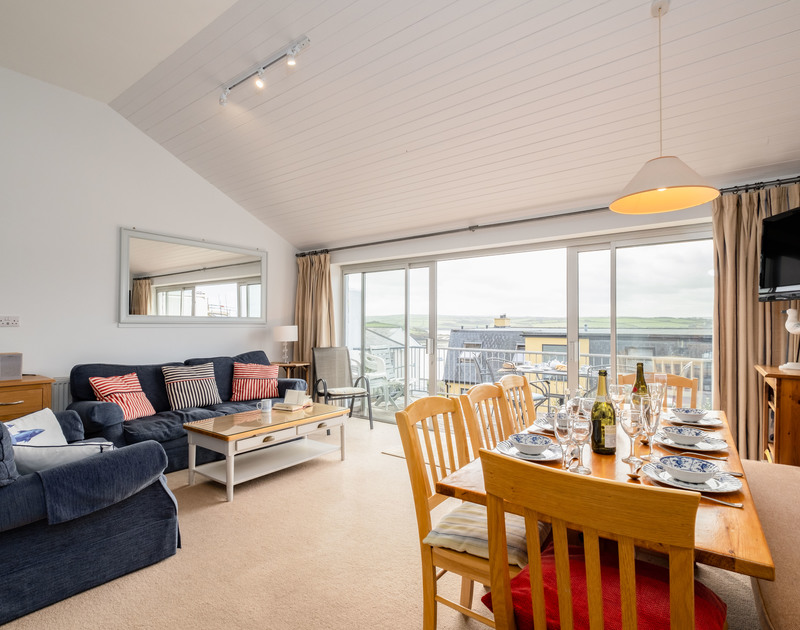 The open plan kitchen, living room and dining area with doors onto the balcony and Camel estuary views at Slipway 7 self catering holiday home in Rock, North Cornwall.