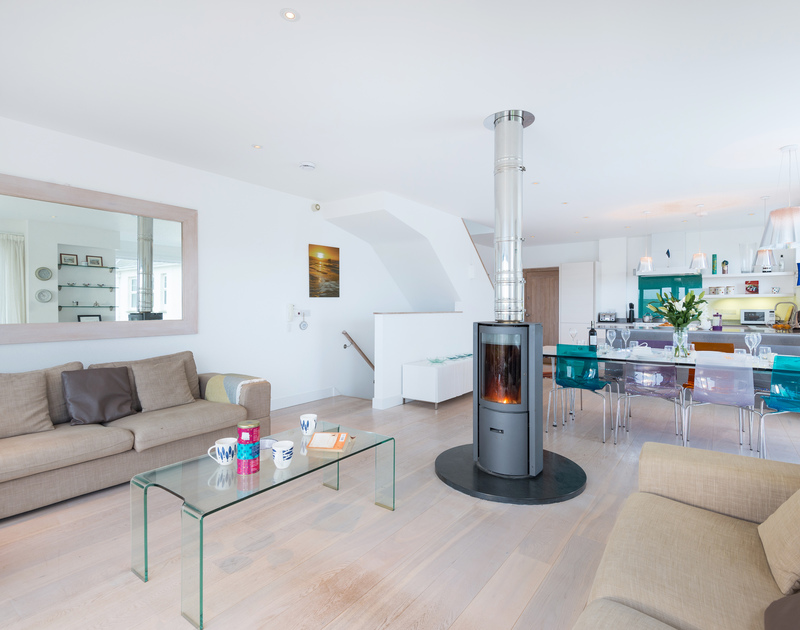 The revolving wood burner in the living space at Stepper Point self catering holiday home in Polzeath, North Cornwall.
