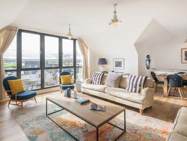 The stylish living room with estuary views at First Light self catering holiday home in Rock, North Cornwall.