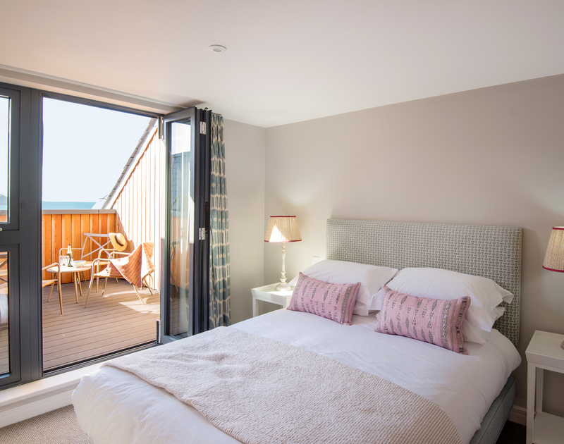 The master bedroom with private decked balcony, ensuite bathroom and sea views at Greenaway self catering apartment holiday home in New Polzeath, North Cornwall.
