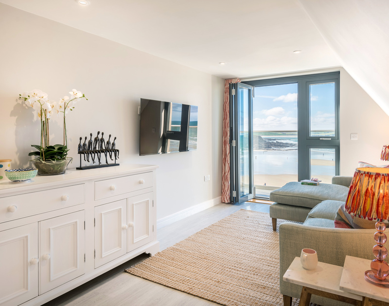 The living room with a balcony and amazing sea views over Polzeath beach at Greeenaway Apartment 8 Atlantic House self catering holiday home in New Polzeath, North Cornwall.