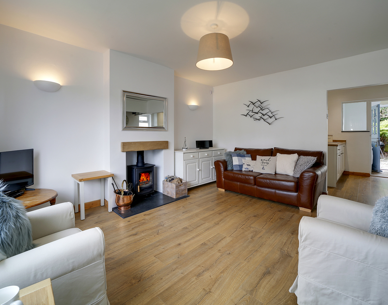The lounge with a cosy wood burner at Little Sark self catering holiday home in Port Isaac, North Cornwall.