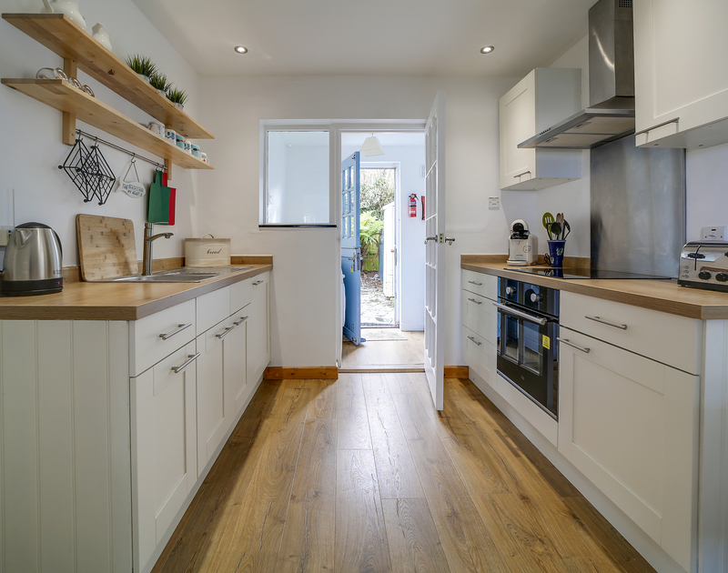 The well-equipped kitchen with access to the back courtyard at Little Sark self catering holiday home in Port Isaac, North Cornwall.