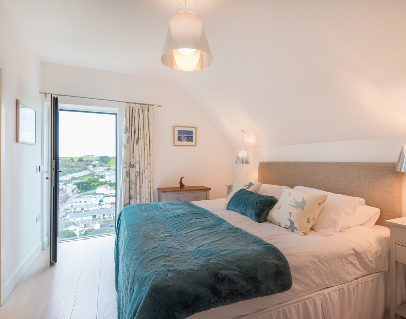 The master bedroom with en suite bathroom and Juliette balcony with sea views at Stepper Point self catering holiday home in Polzeath, North Cornwall.