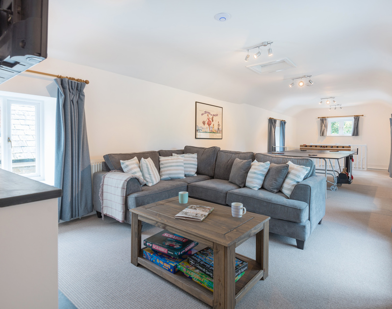 The living room with games area at Orchard Cottage self catering holiday home in Trelights, Port Isaac, North Cornwall.