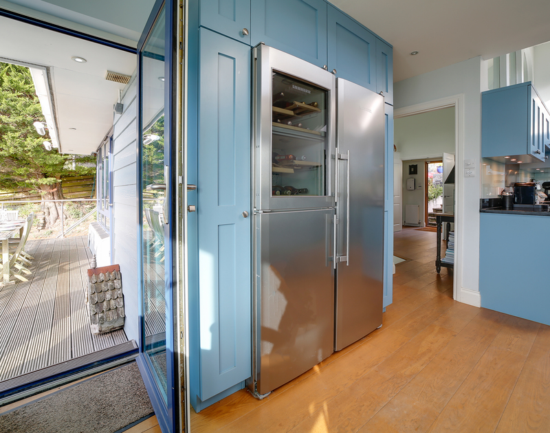 The large fridge and doors out to the deck at Camel Point self catering holiday home in Rock, North Cornwall.